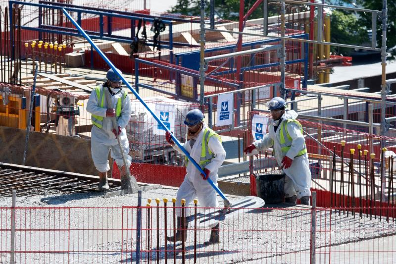 "Construction workers wearing PPE (personal protective equipment), some including face masks, work to build new apartments and a retail complex at Nine Elms in south London on May 12, 2020, as life in Britain continues during the nationwide lockdown due to the novel coronavirus pandemic. - The British government on Monday published what it said was a ""cautious roadmap"" to ease the seven-week coronavirus lockdown in England, notably recommending people wear facemasks in some public settings. They also encouraged those working in construction, manufacturing and other manual jobs to return to work, while recommending those able to work from home to continue to do so. (Photo by JUSTIN TALLIS / AFP) (Photo by JUSTIN TALLIS/AFP via Getty Images)"