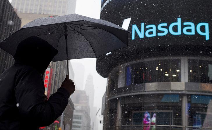 A man uses an umbrella to guard against snowfall as he walks past the Nasdaq MarketSite in Times Square, Midtown New York