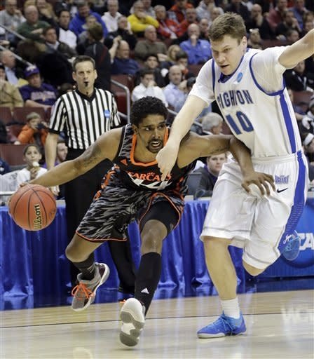 Cincinnati's JaQuon Parker, left, dribbles past Creighton's Grant Gibbs during the first half of a second-round game of the NCAA college basketball tournament, Friday, March 22, 2013, in Philadelphia. (AP Photo/Matt Slocum)