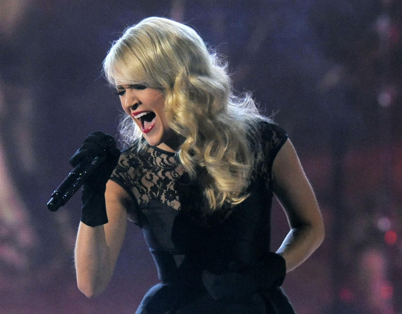 "FILE - This April 7, 2013 file photo shows Carrie Underwood performing at the 48th Annual Academy of Country Music Awards at the MGM Grand Garden Arena in Las Vegas. Underwood will take over the theme song for ""Sunday Night Football,"" with NBC sticking to the formula of a female country music star for its intro. Underwood steps in for Faith Hill, who announced last month that she would not be back for a seventh season. Underwood will sing a new version of ""Waiting All Day for Sunday Night,"" the network said Tuesday, May 7. (Photo by Chris Pizzello/Invision/AP, file)"