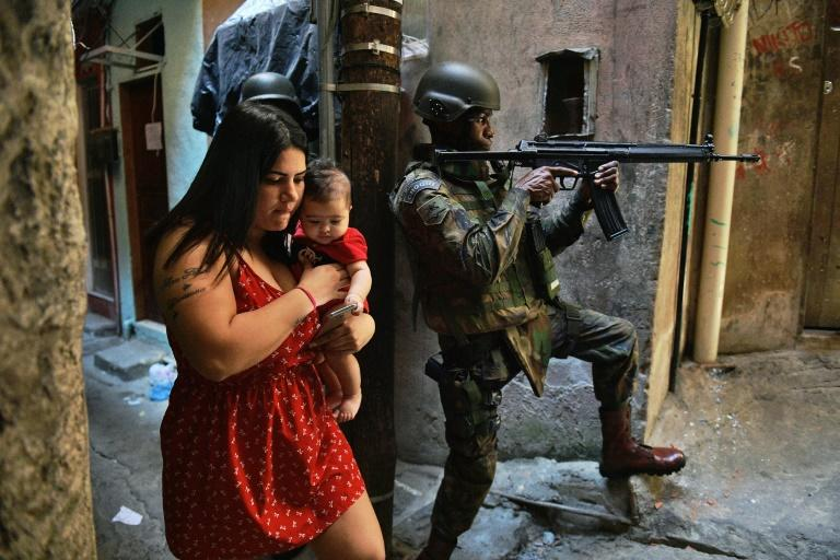 A woman walks with her baby in Rio de Janeiro's Rocinha favela after the deployment of soldiers to reinforce security in September 2017