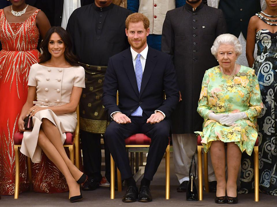 TOPSHOT - (L-R) Meghan, Duchess of Sussex, Britain's Prince Harry, Duke of Sussex and Britain's Queen Elizabeth II pose for a picture during the Queen's Young Leaders Awards Ceremony on June 26, 2018 at Buckingham Palace in London. (Photo by John Stillwell / POOL / AFP)        (Photo credit should read JOHN STILLWELL/AFP via Getty Images)