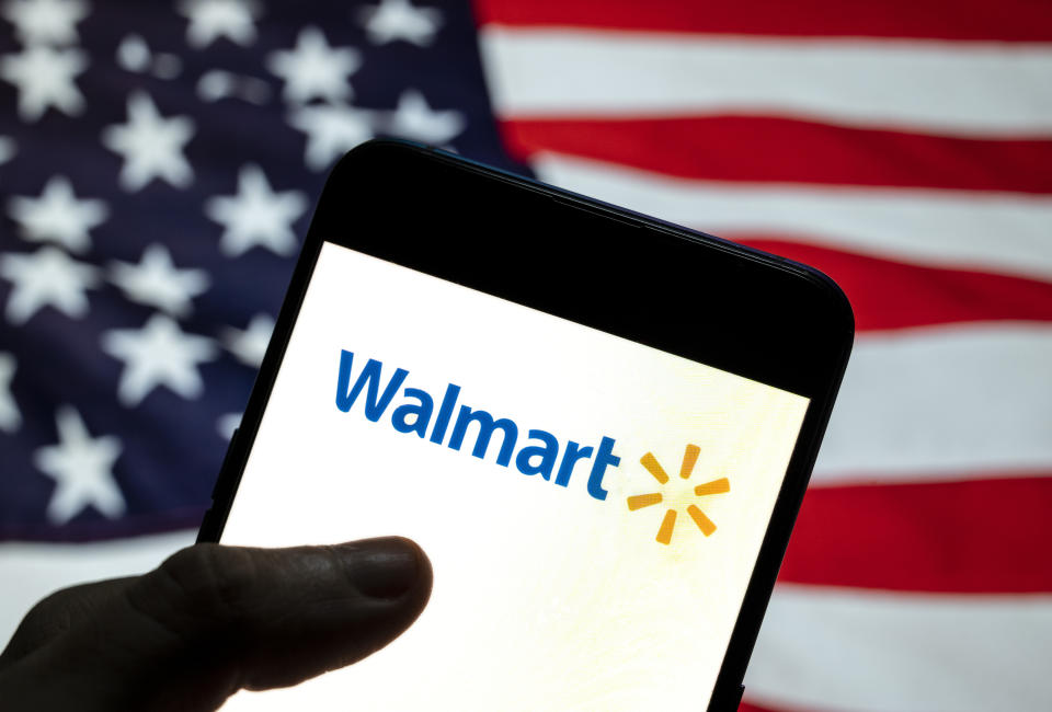 CHINA - 2021/04/02: In this photo illustration the American multinational department stores Walmart logo is seen on an Android mobile device with United States of America (USA), commonly known as the United States (U.S. or US), flag in the background. (Photo Illustration by Budrul Chukrut/SOPA Images/LightRocket via Getty Images)