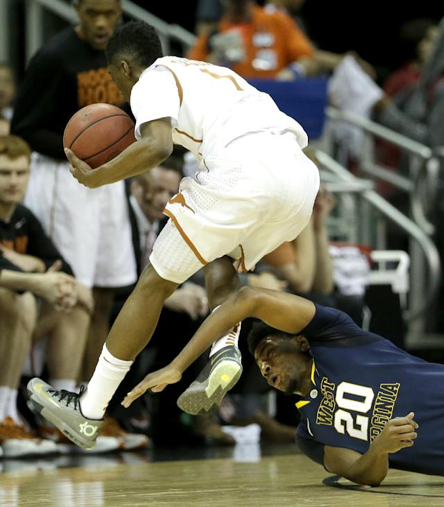 Texas' Isaiah Taylor (1) and West Virginia's Brandon Watkins (20) chase a loose ball during the first half of an NCAA college basketball game in the Big 12 men's tournament on Thursday, March 13, 2014, in Kansas City, Mo. (AP Photo/Charlie Riedel)