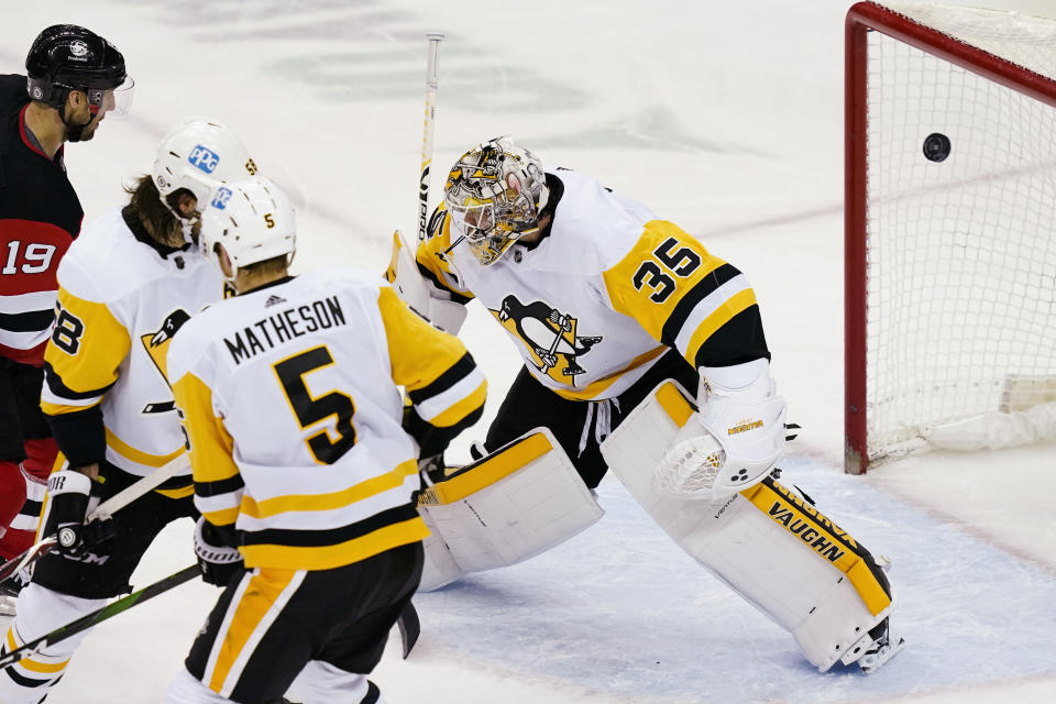 The puck enters the net behind Pittsburgh Penguins goaltender Tristan Jarry (35) on a goal by New Jersey Devils defenseman Damon Severson, not seen, during the second period of an NHL hockey game Thursday, March 18, 2021, in Newark, N.J. (AP Photo/John Minchillo)
