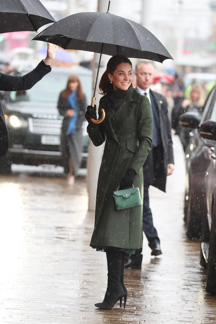 The Duchess of Cambridge kept chic in the rain during a trip to Blackpool courtesy of a belted Sportmax coat. She finished the ensemble with a £158 Michael Kors dress and matching £430 Manu Atelier handbag. [Photo: Getty]