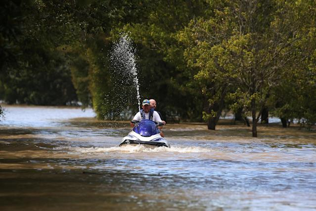 People ride a watercraft though floodwater Wednesday ina neighborhood west of Houston. (Carlo Allegri/Reuters)