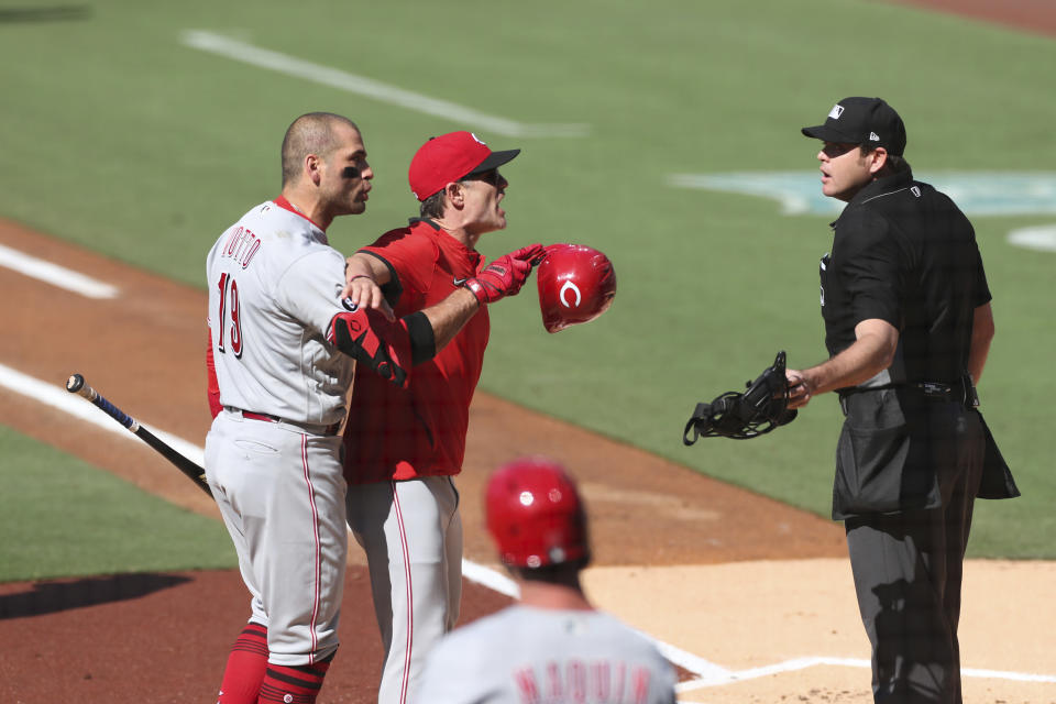 Cincinnati Reds' Joey Votto (19) is held back by manager David Bell, center, while arguing with umpire Ryan Additon after being called out on a checked swing in the first inning of a baseball game against the San Diego Padres, Saturday, June 19, 2021, in San Diego. (AP Photo/Derrick Tuskan)
