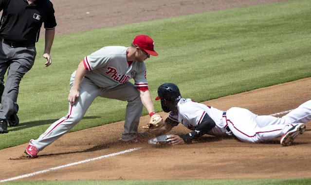 Atlanta Braves right fielder Jason Heyward (22) steals third base as Philadelphia Phillies third baseman Cody Asche (25) applies the late tag in the first inning of a baseball game Monday, Sept. 1, 2014, in Atlanta. (AP Photo/John Bazemore)