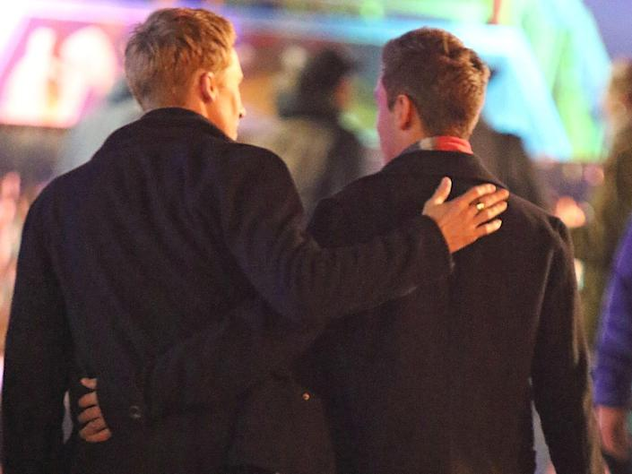 Dustin Lance Black and Tom Daley walking away from camera with backs facing us
