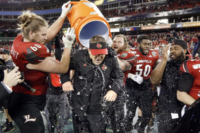 Louisville head coach Scott Satterfield gets dunked with water by offensive lineman Tyler Haycraft (60) in the final moments of the fourth quarter of Louisville's win over Mississippi State in the Music City Bowl NCAA college football game Monday, Dec. 30, 2019, in Nashville, Tenn. Louisville won 38-28. (AP Photo/Mark Humphrey)