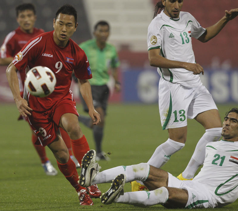 FILE - In Jan. 19, 2011 file photo, North Korea's player Jong Tae Se, left, fights for the ball with Iraq's player Ahmed Ibrahim during their AFC Asian Cup group D soccer match at Al-Rayyan Stadium, in Doha, Qatar.  South Korean club, The Suwon Samsung Bluewings said Thursday, Jan. 3, 2013 it has acquired North Korea striker Jong from Germany's Cologne. (AP Photo/Kin Cheung, File)
