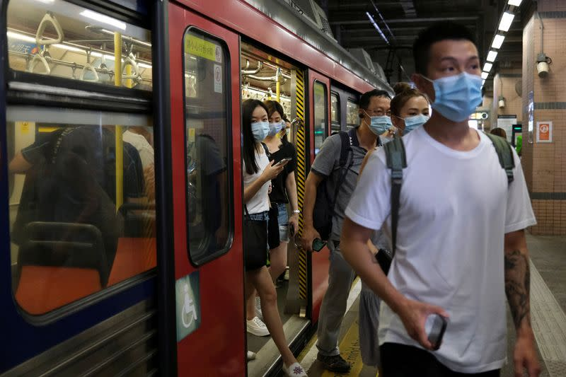 FILE PHOTO: People wear protective face masks at a Light Rail station following the coronavirus disease (COVID-19) outbreak in Hong Kong