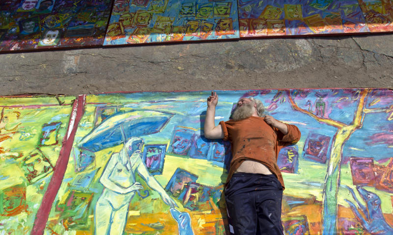 In this photo taken on April 4, 2013, Romanian artist Vasile Muresan-Murivale poses on one of his paintings in a parking lot, in Bucharest, Romania. The white-bearded painter can often be seen sitting on his colorful canvasses which he displays in the street followed by the street dogs which are his companions and also inspire his work. The 56-year-old, whose home city is Bistrita_the Transylvanian town associated with the legendary Count Dracula_ has been painting with passion since he was a teen, producing vivid works of Monaco, the streets of Paris, the hurly burly of the Romanian capital and huge colorful more abstract canvasses. (AP Photo/Vadim Ghirda)