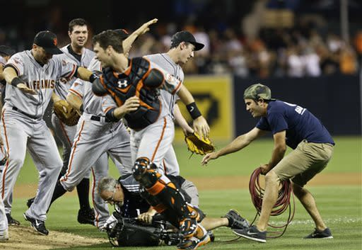 San Francisco Giants starting pitcher Tim Lincecum, right, steps out of the pile of players celebrating his no hitter against the San Diego Padres as a television cameraman hits the ground in a baseball game in San Diego, Saturday, July 13, 2013. Tim Lincecum has thrown his first career no-hitter and the second in the majors in 11 days, a gem saved by a spectacular diving catch by right fielder Hunter Pence in the San Francisco Giants' 9-0 win against the last-place San Diego Padres on Saturday night. (AP Photo/Lenny Ignelzi)