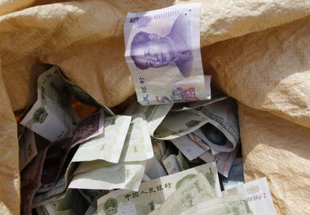 Chinese Yuan bank notes are seen in a vendor's cash sack at a market in Beijing
