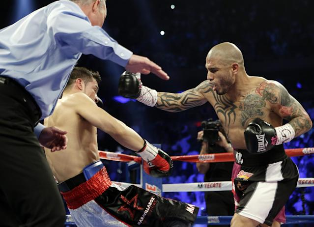 Miguel Cotto, of Puerto Rico, knocks down Sergio Martinez, of Argentina, during the first round of a WBC middleweight title boxing match Saturday, June 7, 2014, in New York. (AP Photo/Frank Franklin II)