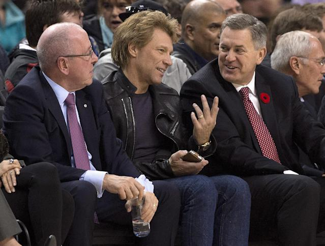 Maple Leaf Sports and Entertainment CEO Tim Leiweke, right, chats with Jon Bon Jovi as MLSE Chairman Larry Tanenbaum listens during the first half of an NBA basketball game between the Boston Celtics and the Toronto Raptors on Wednesday, Oct. 30, 2013, in Toronto. (AP Photo/The Canadian Press, Frank Gunn)