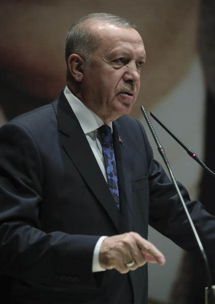 "Turkey's President Recep Tayyip Erdogan addresses the members of his ruling party, in Ankara, Turkey, Thursday, Dec. 26, 2019. Erdogan says Thursday his government will submit a bill to parliament that would allow Turkey to send troops to Libya, in support of the U.N.-backed government there. Erdogan said the Libyan government, which controls the capital, Tripoli, has ""invited"" Turkey to send troops. (Turkish Presidency via AP, Pool)"