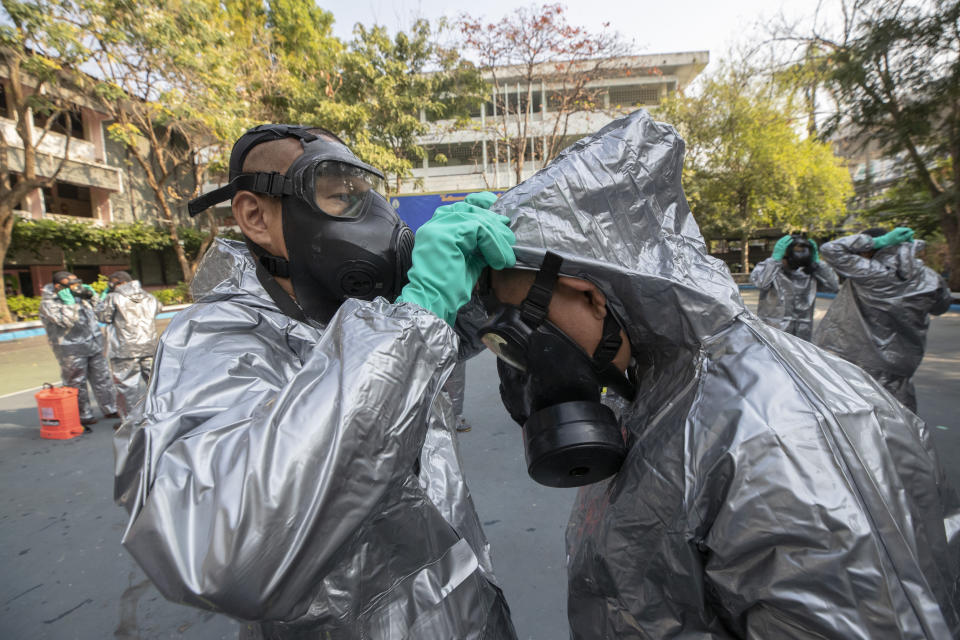 Soldiers from Royal Thai Army Chemical Department prepare to spray disinfectant as a precaution against the coronavirus at Bang Bua school in Bangkok, Thailand, Tuesday, Jan. 26, 2021. (AP Photo/Sakchai Lalit)