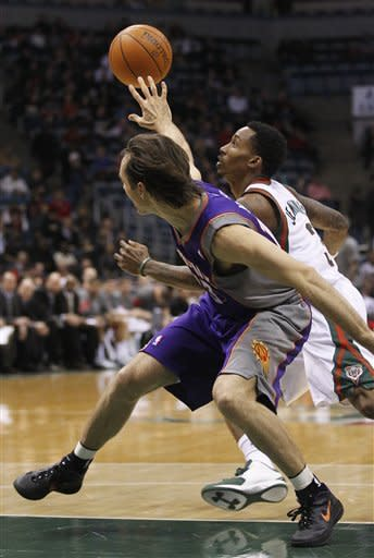 Phoenix Suns' Steve Nash, front, loses the ball to Milwaukee Bucks' Brandon Jennings (3) during the first half of an NBA basketball game on Tuesday, Feb. 7, 2012, in Milwaukee. (AP Photo/Jeffrey Phelps)