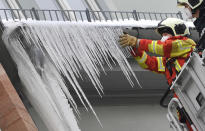 Firefighters break large icicles from the gutter of a house in the city centre of Erfurt, Germany, Thursday, Feb.11, 2021. Arctic polar air continues to cause severe frost in Germany. (Martin Schutt/dpa via AP)