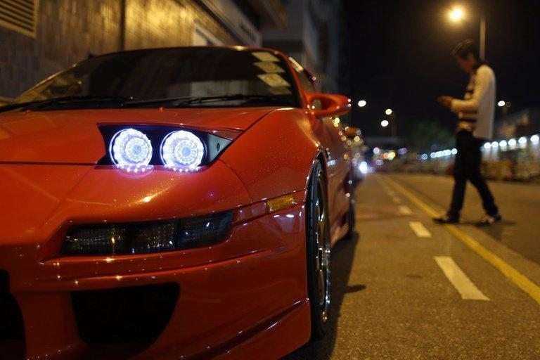 A man walks past modified racing cars before a race in the early hours of the morning in Hong Kong, on April 7, 2013. As night begins to give way to dawn, 40 high-performance cars pull up on an empty Hong Kong backstreet. Their revving engines fill the air with a heavy smell of petrol as the city sleeps