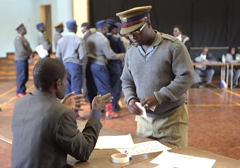 A Zimbabwean police officer speaks to an official, before casting his vote, at a polling station, in Harare, Monday, July, 15, 2013. Officials of Zimbabwe's election commission said Sunday early voting started for police and security personnel who will be on duty during the nation's crucial elections on July 31. (AP Photo/Tsvangirayi Mukwazhi)