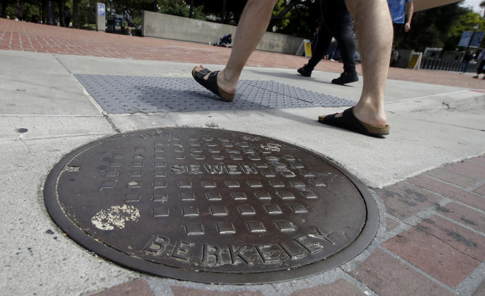 """Pedestrians walk past a manhole cover for a sewer in Berkeley, Calif., Thursday, July 18, 2019. Soon students in Berkeley, California will have to pledge to """"collegiate Greek system residences"""" instead of sororities or fraternities and city workers will have to refer to manholes as """"maintenance holes."""" Officials in the liberal city this week passed an ordinance to replace some terms with gender-neutral words in the city code. (AP Photo/Jeff Chiu)"""