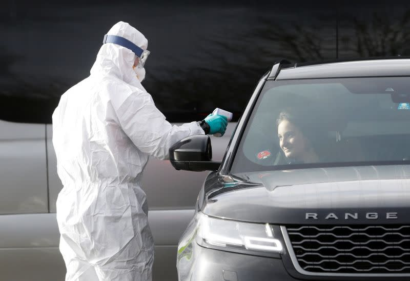 A police officer in a protective suit checks the temperature of a person inside a car at Czech-German border in Rozvadov crossing