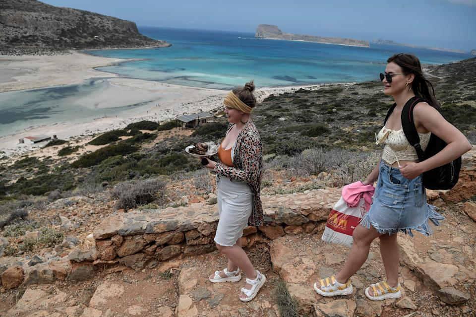 Tourists carry their meals as they walk towards the Balos beach and its lagoon on the north-eastern part of the island of Crete, Greece. Photo: Louisa Gouliamaki/AFP via Getty Images