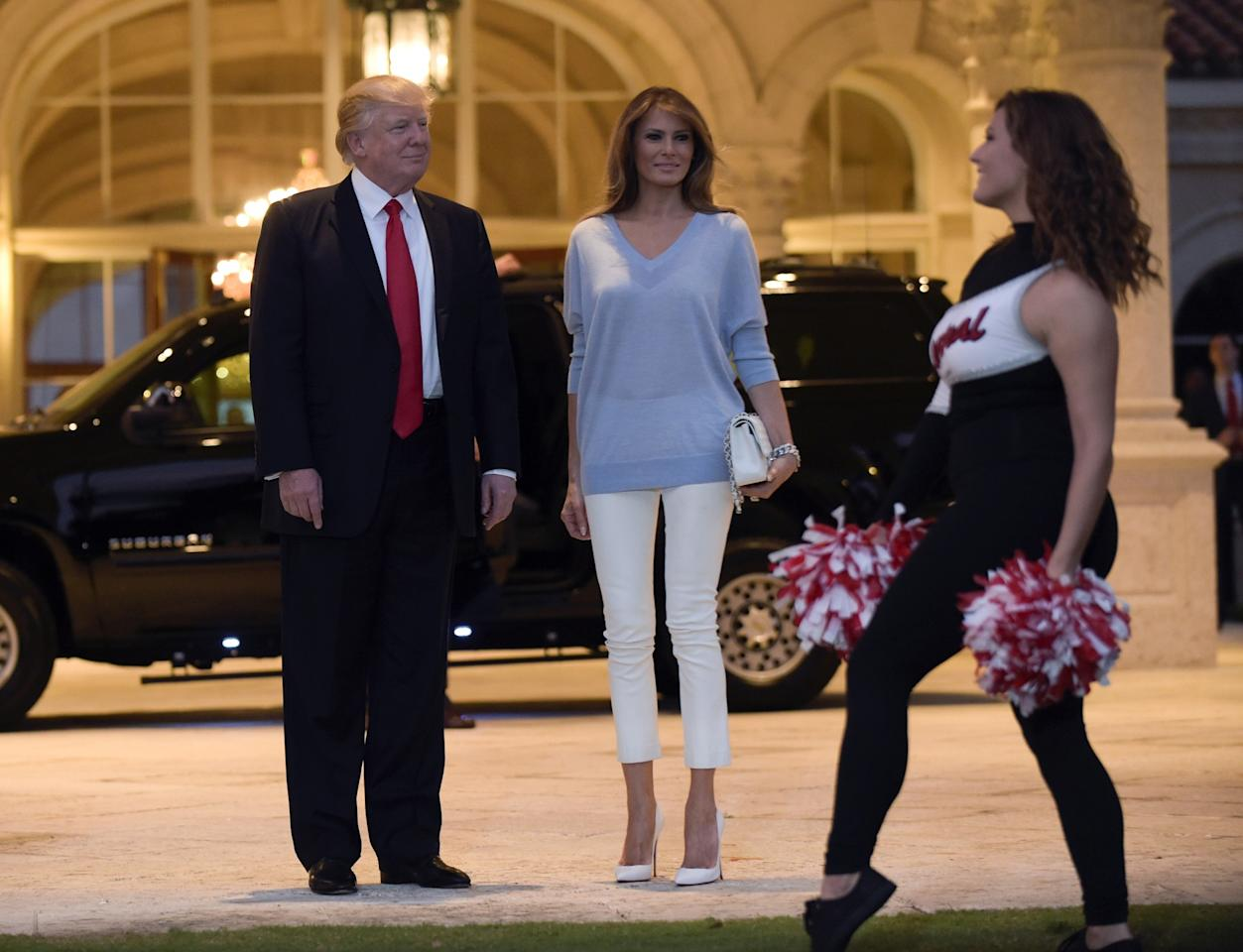 """<p>To watch the Super Bowl at a viewing party hosted by her husband, a Patriots fan because of his friendship with Tom Brady and Robert Kraft, Melania Trump dressed in the Palm Beach version of patriotic colors: cropped white pants and light blue sweater (and red blush to complete the look). The Double V-neck felted lambswool sweater in light blue comes from Victoria Beckham and retails for $1,100. She accessorized with Chanel's classic quilted flap bag in white ($4,495) and matching """"So Kate"""" Christian Louboutin pumps ($695). (Photo: AP) </p>"""