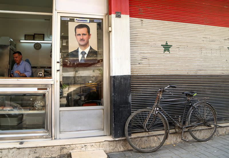 FILE PHOTO: A picture of Syrian President Bashar al-Assad is seen on a door of a butcher shop, during a lockdown to prevent the spread of the coronavirus disease (COVID-19), in Damascus