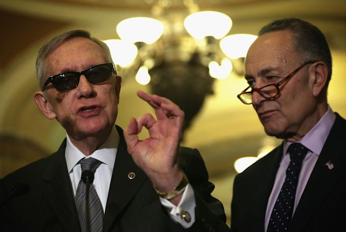 U.S. Senate Minority Leader Harry Reid (D-Nev.) (left) speaks as Sen. Charles Schumer (D-N.Y.) listens during a news briefing after the weekly Senate Democratic Policy Luncheon on Feb. 24, 2015. Reid was wearing glasses following a recent eye surgery.
