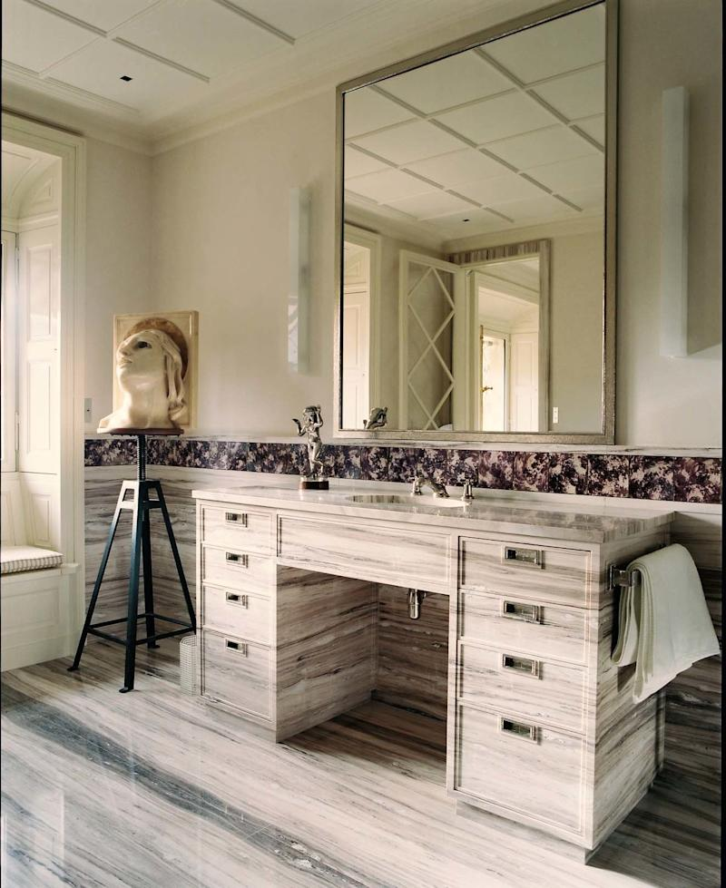 A palissandro marble vanity designed by Grange anchors the master bath.