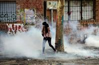 A woman runs away from tear gas after a protest in Santiago turned violent