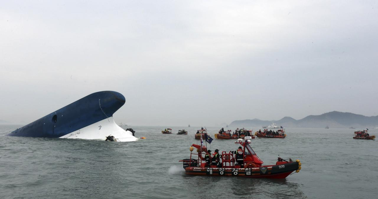 "Part of South Korean passenger ship ""Sewol"" that has been sinking is seen as South Korean maritime policemen search for passengers in the sea off Jindo April 16, 2014. More than 100 people remained missing on Wednesday after a South Korean ferry with 477 people aboard capsized off the country's southwest coast, Yonhap news agency said. REUTERS/Hyung Min-woo/Yonhap (SOUTH KOREA - Tags: DISASTER MARITIME) 