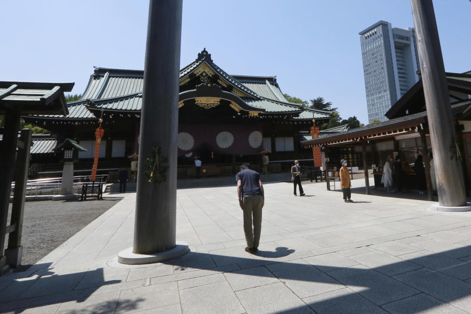 A worshipper bows at Yasukuni Shrine in Tokyo, Wednesday, April 21, 2021, the first day of the annual Spring Rites, the Shinto shrine's biannual festival honoring the war dead. (AP Photo/Koji Sasahara)