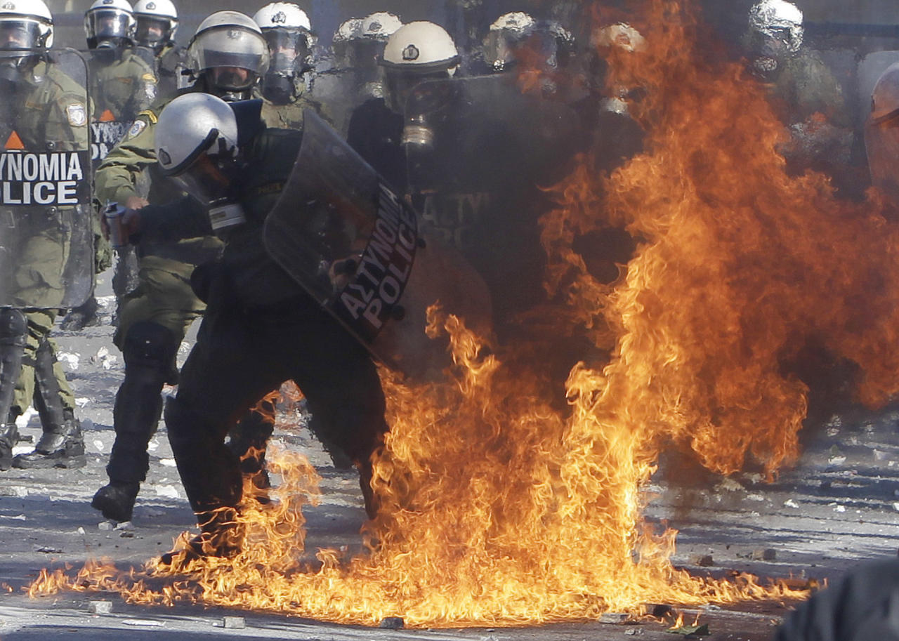 A riot policeman's clothing catches fire after being hit by a petrol bomb during clashes outside the Greek parliament in Athens, Wednesday, Oct. 19, 2011. Greek anger over new austerity measures and layoffs erupted into violence outside parliament on Wednesday, as demonstrators hurled chunks of marble and gasoline bombs and riot police responded with tear gas and stun grenades that echoed across Athens' main square. Wednesday was the first day of a two-day general strike that unions described as the largest protests in years, with at least 100,000 people marching through central Athens. (AP Photo/Thanassis Stavrakis)