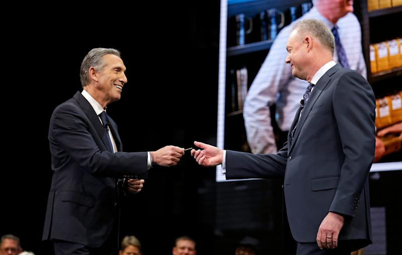 Howard Schultz, left, hands over the door key of the Pike Place Market Starbucks' store to Kevin Johnson at the company's annual shareholders meeting, Wednesday, March 22, 2017, in Seattle. (AP Photo/Elaine Thompson)