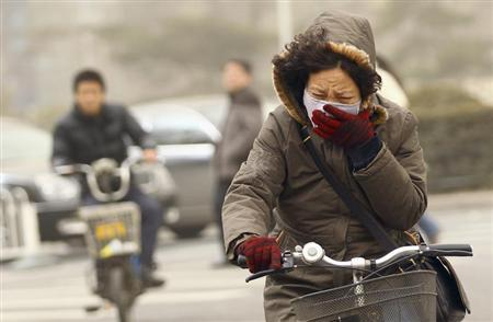 A woman wearing a mask rides her bicycle along a street on a hazy morning in Beijing