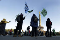 Supporters of the 'Extinction Rebellion' movement block a road at the Victory Column in Berlin, Germany, Monday, Oct. 7, 2019. The activists want to draw attention on the climate protest by blocking roads and with other acts of civil disobedience in Berlin and other cities around the world. (AP Photo/Michael Sohn)
