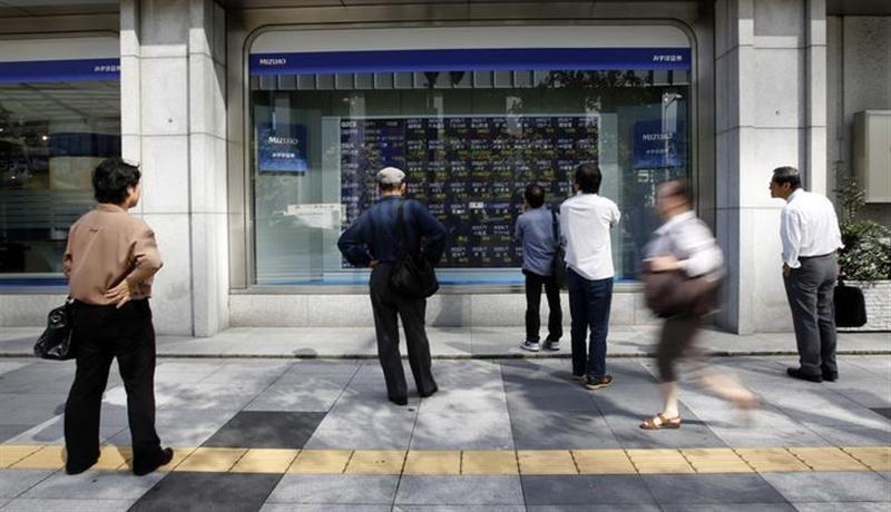 Pedestrians look at a stock quotation board displaying various stock prices outside a brokerage in Tokyo October 11, 2013.