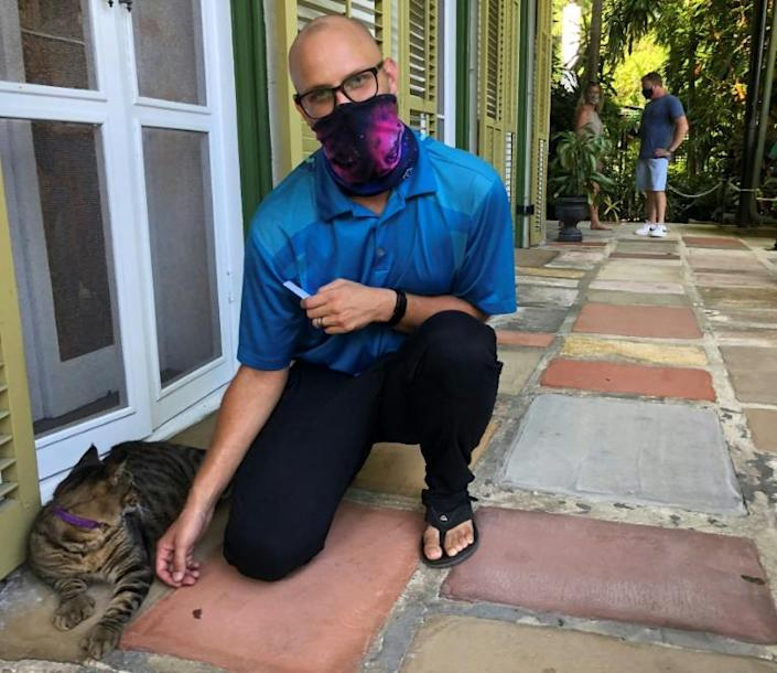 Andrew Morawski, director of the Ernest Hemingway Home and Museum, pets Joe DiMaggio, one of the six-toed cats that live in the late author's house in Key West, Florida on August 30, 2020
