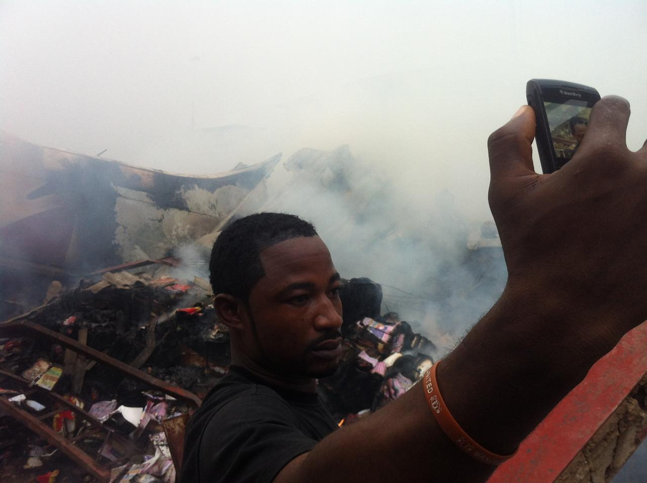 A man uses a cell phone to photograph himself in front of the wreckage of a passenger plane that crashed into buildings in a neighborhood just north of Murtala Muhammed International Airport, in Lagos, Nigeria, Sunday, June 3, 2012. The passenger plane carrying more than 150 people crashed in Nigeria's largest city on Sunday, government officials said. The Lagos state government said in a statement that 153 people were on the Dana Air flight Sunday.(AP Photo/Jon Gambrell)