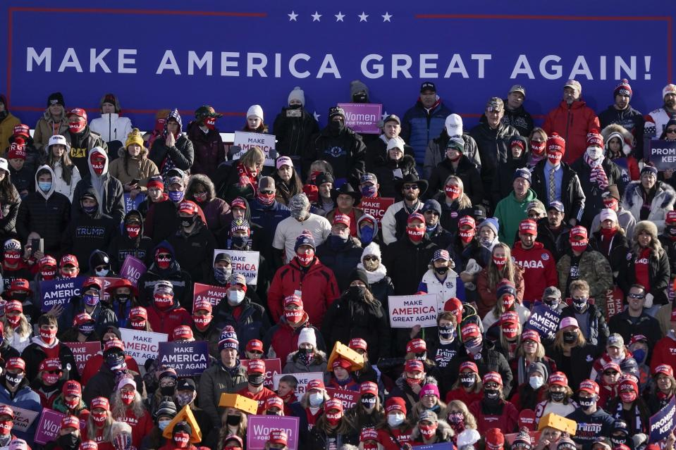 Supprters listen as President Donald Trump speaks at a campaign rally Friday, Oct. 30, 2020, at the Austin Straubel Airport in Green Bay, Wis. (AP Photo/Morry Gash)