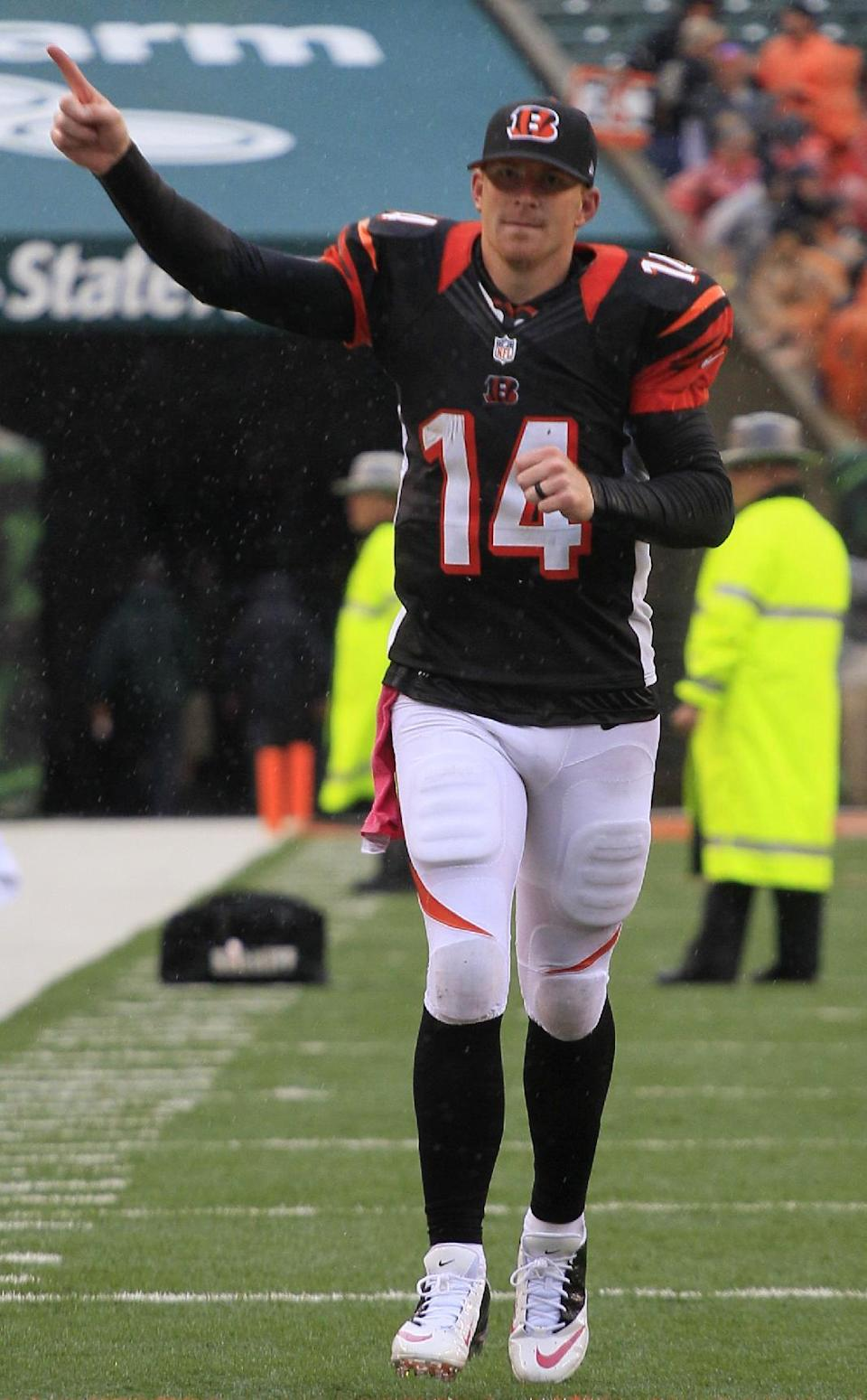 Cincinnati Bengals quarterback Andy Dalton runs off the field after the Bengals defeated the New England Patriots 13-6 in an NFL football game on Sunday, Oct. 6, 2013, in Cincinnati. (AP Photo/Tom Uhlman)