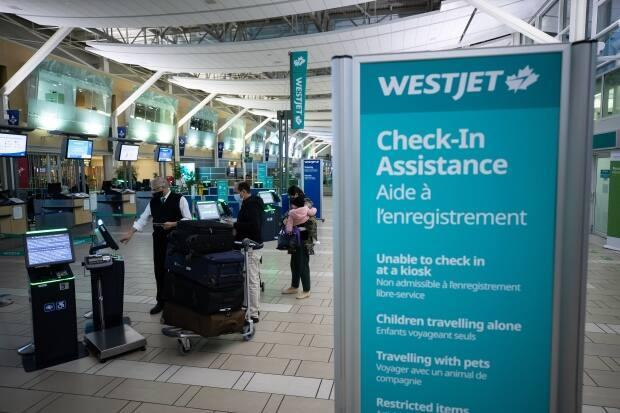 A WestJet employee assists people checking in for a domestic flight at Vancouver International Airport on Jan. 21, 2021. WestJet will require all employees to be vaccinated for COVID-19, in line with the federal government's requirements for the air travel industry.  (Darryl Dyck/The Canadian Press - image credit)
