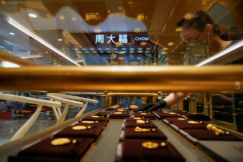 A salesperson poses with Heritage Gold jewellery at jeweller Chow Tai Fook's retail store in Shanghai
