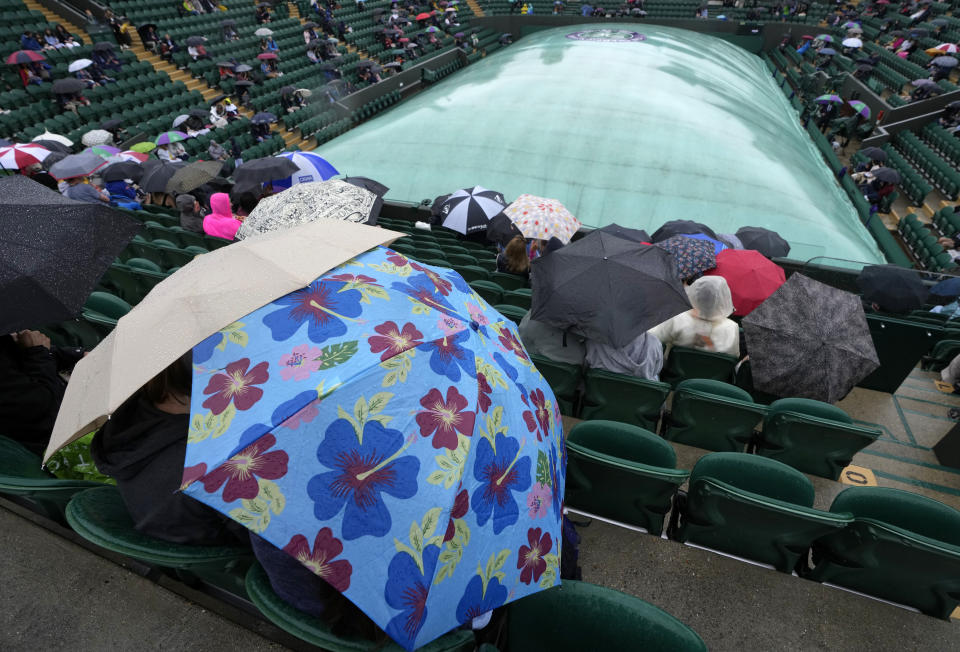 People shelter under umbrellas on Court 2 during a rain delay on day one of the Wimbledon Tennis Championships in London, Monday June 28, 2021. (AP Photo/Kirsty Wigglesworth)